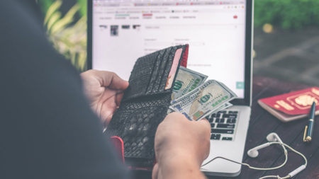 person holding money in front of laptop screen
